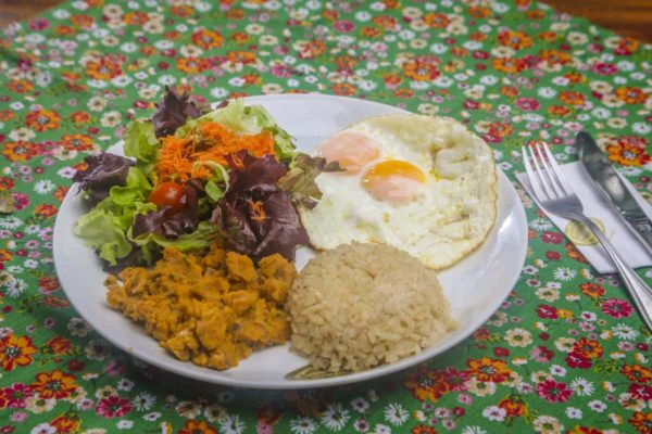 Sunny side up eggs with whole grain rice, pinto beans, baked manioc flour with beans